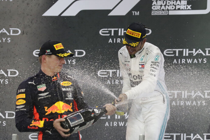 Mercedes driver Lewis Hamilton of Britain, right, celebrates on the podium after wining the Emirates Formula One Grand Prix, with second place Red Bull driver Max Verstappen of the Netherland's at the Yas Marina racetrack in Abu Dhabi, United Arab Emirates, Sunday, Dec.1, 2019. (AP Photo/Hassan Ammar)