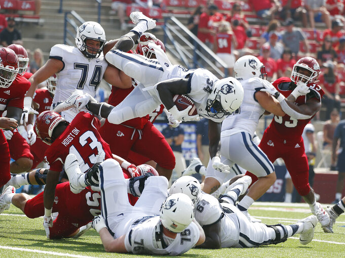 Connecticut running back Kevin Mensah (34) goes up high for a short gain against Fresno State during the first half of an NCAA college football game in Fresno, Calif., Saturday, Aug. 28, 2021. (AP Photo/Gary Kazanjian)