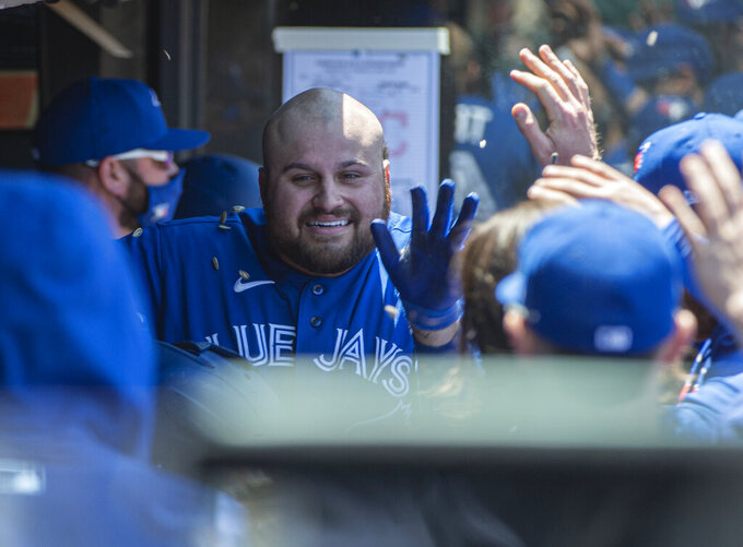Toronto Blue Jays' Rowdy Tellez is greeted by his teammates after hitting a solo home run off Cleveland Indians starting pitcher Aaron Civale during the fourth inning of the first baseball game of a doubleheader in Cleveland, Sunday, May 30, 2021. (AP Photo/Phil Long)