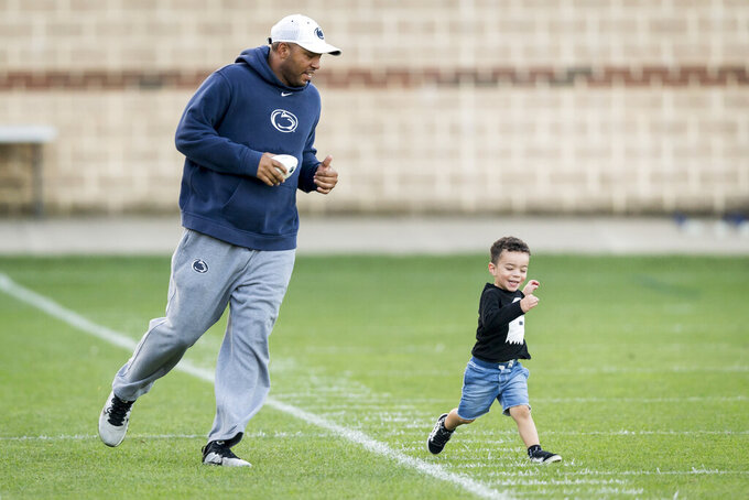 FILE - In this Sept. 27, 2017, file photo, then-Penn State wide receivers coach Josh Gattis chases his son Jace, 2, following NCAA college football practice, in State College, Pa. Michigan hired Josh Gattis away from Alabama to be Jim Harbaugh's offensive coordinator on Thursday, Jan. 19, 2019. The 34-year-old Gattis was a co-offensive coordinator last season for the Crimson Tide. Gattis was Penn State's wide receivers coach and passing-game coordinator and led the program's offensive recruiting efforts the previous four seasons. (Joe Hermitt/The Patriot-News via AP, File)