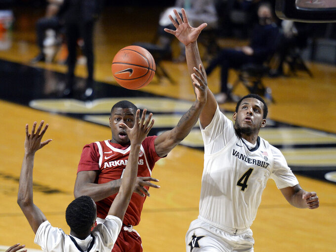 Arkansas guard Davonte Davis (4) passes the ball as he is defended by Vanderbilt guard's Trey Thomas, left, and Jordan Wright (4) during the second half of an NCAA college basketball game against Vanderbilt Saturday, Jan. 23, 2021, in Nashville, Tenn. Arkansas won 92-71. (AP Photo/Mark Zaleski)