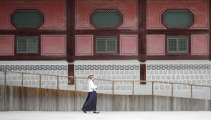 A woman wearing a face mask walks outside of Heungnyemun gate of the 14th-century Gyeongbok Palace, and one of South Korea's well-known landmarks, in Seoul, South Korea, Friday, June 19, 2020. (AP Photo/Lee Jin-man)