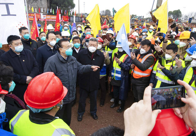 In this photo released by China's Xinhua News Agency, Chinese Premier Li Keqiang, fourth left, speaks with construction workers at the site of makeshit field hospital being built in Wuhan in central China's Hubei province, Monday, Jan. 27, 2020. China on Monday expanded its sweeping efforts to contain a deadly virus, extending the Lunar New Year holiday to keep the public at home and avoid spreading infection. (Li Tao/Xinhua via AP)