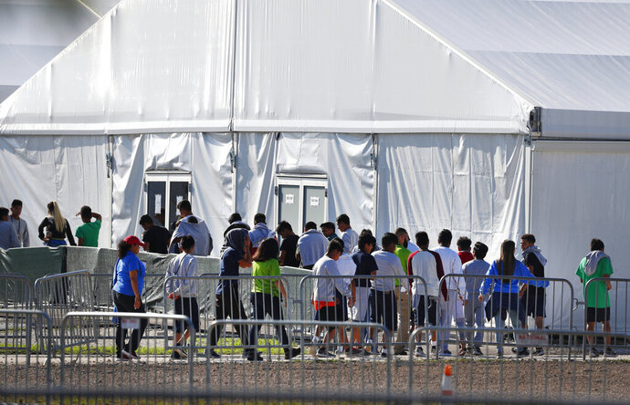FILE- In this Feb. 19, 2019 file photo, children line up to enter a tent at the Homestead Temporary Shelter for Unaccompanied Children in Homestead, Fla. The Trump administration is shutting down operations at one of the largest U.S. facilities for child migrants that had come under intense criticism from advocates and lawmakers. The U.S. Department of Health and Human Services said it reduced bed capacity from 1,200 to zero at the Homestead, Florida site. About 2,000 workers were being let go. (AP Photo/Wilfredo Lee, File)