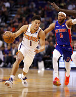 Phoenix Suns guard Devin Booker (1) drives as Detroit Pistons guard Bruce Brown (6) pursues during the second half of an NBA basketball game Thursday, March 21, 2019, in Phoenix. (AP Photo/Matt York)