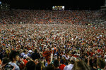 FILE - In this Nov. 30, 2019, file photo, Auburn fans storm the field after they defeated Alabama 48-45 in an NCAA college football game in Auburn, Ala. For the fans, team owners, sponsors and just about everyone else associated with college and professional sports, the coronavirus pandemic has forced changes both big and small. The most obvious change in the short term will be the implementation of social distancing. (AP Photo/Butch Dill, File)