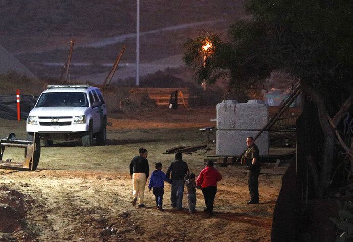 Migrants traveling with children walk up a hill to a waiting U.S. Border Patrol agent just inside San Ysidro, Calif., after climbing over the border wall from Playas de Tijuana, Mexico, Monday, Dec. 3, 2018. Thousands of Central American migrants who traveled with recent caravans want to seek asylum in the United States but face a decision between crossing illegally or waiting months, because the U.S. government only processes a limited number of those cases a day at the San Ysidro border crossing. (AP Photo/Rebecca Blackwell)