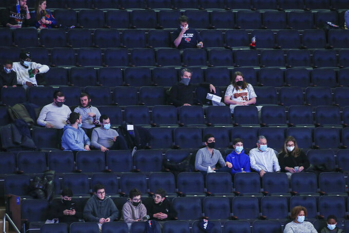 Fans watch the New York Knicks play against the Golden State Warriors in an NBA basketball game Tuesday, Feb. 23, 2021, in New York. For the first time this season, fans were allowed to attend a Knicks home game. (Wendell Cruz/Pool Photo via AP)