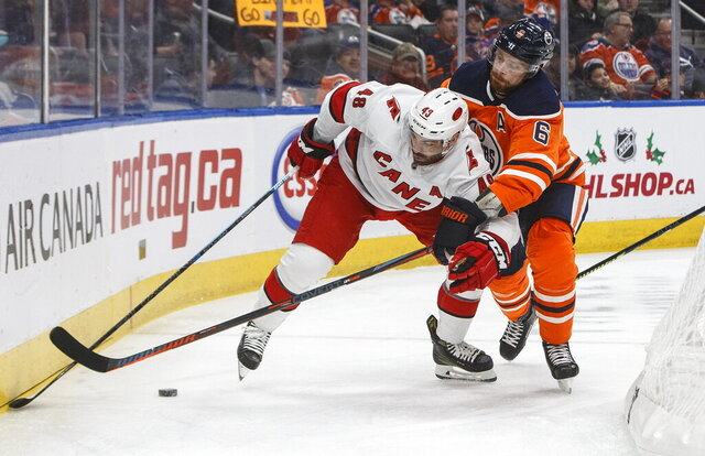 Carolina Hurricanes' Jordan Martinook and Edmonton Oilers' Adam Larsson (6) battle for the puck during the first period of an NHL hockey game, in Edmonton, Alberta, Tuesday, Dec. 10, 2019. (Jason Franson/The Canadian Press via AP)