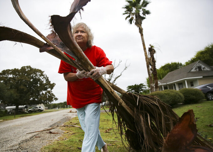 Alfa Alamia cleans up her brother's yard in Palacios, Texas following Hurricane Nicholas on Tuesday, Sept. 14, 2021. Alamia has lived in Palacios since she was 12. (Elizabeth Conley/Houston Chronicle via AP)