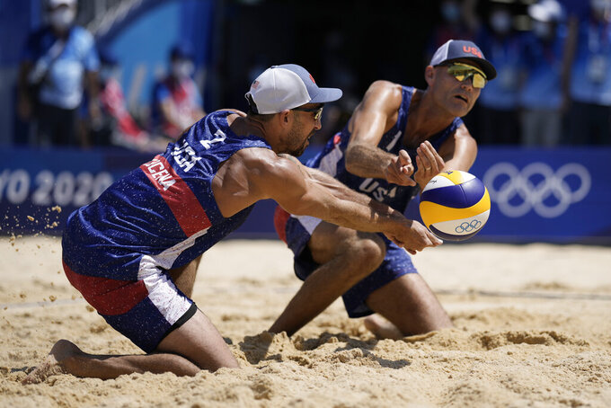 Philip Dalhausser, right, of the United States, and teammate Nicholas Lucena, converge on the ball during a men's beach volleyball match against Qatar at the 2020 Summer Olympics, Sunday, Aug. 1, 2021, in Tokyo, Japan. (AP Photo/Felipe Dana)