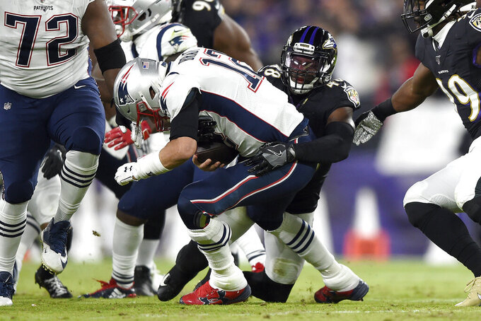 Baltimore Ravens linebacker Patrick Onwuasor, right, sacks New England Patriots quarterback Tom Brady (12) during the first half of an NFL football game, Sunday, Nov. 3, 2019, in Baltimore. (AP Photo/Gail Burton)