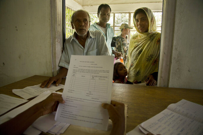 People whose names were left out in the National Register of Citizens (NRC) draft stand to collect forms to file appeals in Mayong, 45 kilometers (28 miles) east of Gauhati, India, Friday, Aug. 10, 2018. A draft list of citizens in Assam, released in July, put nearly 4 million people on edge to prove their Indian nationality. (AP Photo/Anupam Nath)