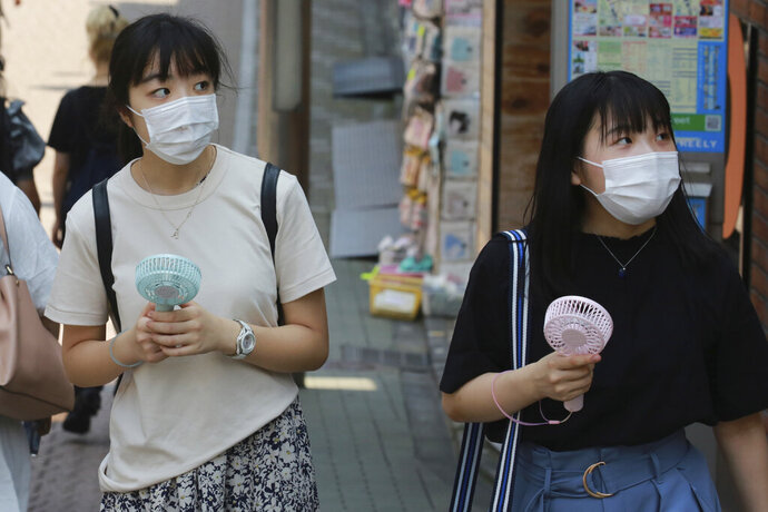 People wearing face masks to help protect against the spread of the coronavirus hold portable fans to cool themselves in the heat in Tokyo, Wednesday, Aug, 5, 2020. (AP Photo/Koji Sasahara)