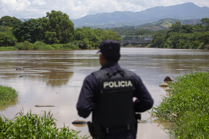 An El Salvadoran national police agent looks out over La Paz River on the border with Guatemala in La Hachadura, El Salvador, Thursday, Sept. 12, 2019, as part of a deployment of 800 police and soldiers to patrol blind spots along its borders where migrant smugglers and transnational criminals operate. The deployment is part of an agreement between the Salvadoran government and acting U.S. Homeland Security Secretary Kevin McAleenan to slow the flow of migrants trying to reach the United States. (AP Photo/Moises Castillo)