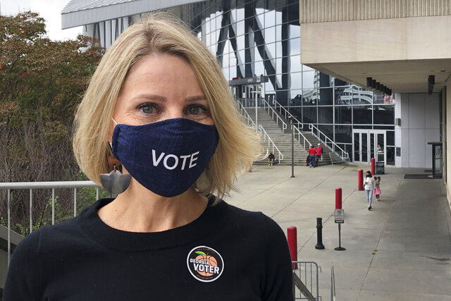 Jen Cox poses for a photo on Thursday, Oct. 15, 2020, after voting early at State Farm Arena in downtown Atlanta. The arena, where the NBA's Atlanta Hawks play, is one of many professional sports venues around the country that has opened its doors for voting or other election-related activities. With dozens of voting machines and ample space for social distancing, they provide a safe and efficient way to vote during the ongoing coronavirus pandemic. (AP Photo/Kate Brumback)