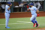 Texas Rangers' Rougned Odor, right, salutes with third base coach Tony Beasley, left, after hitting his second home run of the day in the fifth inning of a baseball game against the Houston Astros in Arlington, Texas, Sunday, Sept. 27, 2020. (AP Photo/Roger Steinman)