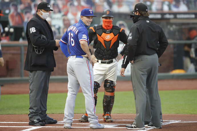 Texas Rangers' Scott Heineman (16) meets his brother Tyler Heineman as they represent their teams with umpires prior to a baseball game Saturday, Aug. 1, 2020, in San Francisco. (AP Photo/Ben Margot)