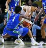 Florida Gulf Coast's Zach Scott grapples for the ball with Virginia Commonwealth's Marcus Santos-Silva during an NCAA college basketball game at Virginia Commonwealth University's Siegel Center in Richmond, Va., Saturday, Nov. 23, 2019. (Joe Mahoney/Richmond Times-Dispatch via AP)