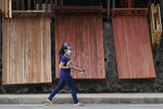 A woman wears a mask to curb the spread of the coronavirus walks past wooden beds for sale at a  roadside stall on the outskirts of Manila, Philippines on Friday, Sept. 25, 2020. (AP Photo/Aaron Favila)