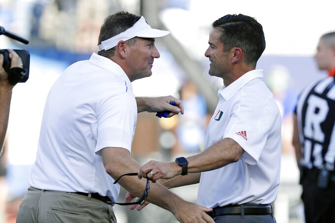 Florida coach Dan Mullen, left, greets Miami coach Manny Diaz before an NCAA college football game Saturday, Aug. 24, 2019, in Orlando, Fla. (AP Photo/John Raoux)