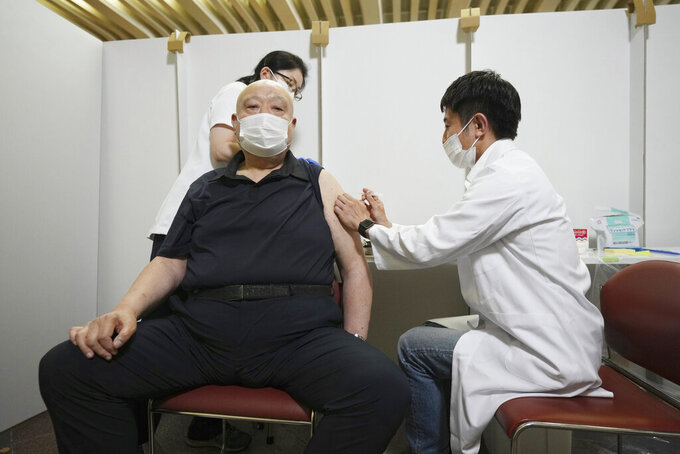 FILE - In this May 24, 2021, file photo, former sumo stable master Chiganoura, left, receives his first dose of Pfizer's COVID-19 vaccine at the Ryogoku Kokugikan sporting arena. The arena, mainly used for sumo wrestling tournaments, is being used as a temporary inoculation venue for residents over 65 years old in Tokyo. Japan, seriously behind in coronavirus vaccination efforts, is scrambling to boost daily shots as the start of the Olympics in July closes in. (AP Photo/Eugene Hoshiko, File)