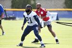 Dallas Cowboys running back Ezekiel Elliott (21) and quarterback Dak Prescott warm up before practice at the NFL football team's training camp in Oxnard, Calif., Thursday, July 22, 2021. (AP Photo/Michael Owen Baker)