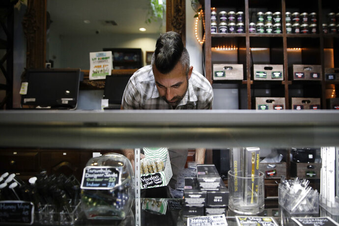 FILE - In this June 27, 2017, file photo, Jerred Kiloh, owner of the licensed medical marijuana dispensary Higher Path, stocks shelves with with cannabis products in Los Angeles. Weedmaps a major online pot shop directory and cannabis marketplace announced Wednesday, Aug. 21, 2019, that it will no longer allow black-market businesses to advertise on its site, a decision that could boost California's efforts to rein in its vast illegal market. Kiloh, who heads the United Cannabis Business Association, an industry group, projected that half of California's illegal operations could dry up once they are denied access to Weedmaps ads. (AP Photo/Jae C. Hong, File)