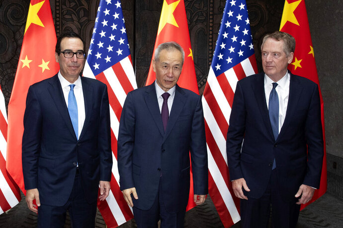Chinese Vice Premier Liu He, center, poses with U.S. Trade Representative Robert Lighthizer, right, and Treasury Secretary Steven Mnuchin, for photos before holding talks at the Xijiao Conference Center in Shanghai Wednesday, July 31, 2019. (AP Photo/Ng Han Guan, Pool)