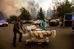 FILE - This Nov. 8, 2018, file photo shows Medical personnel evacuate patients as the Feather River Hospital burns while the Camp Fire rages through Paradise, Calif. Tens of thousands of people fled the fast-moving wildfire. (AP Photo/Noah Berger, File)