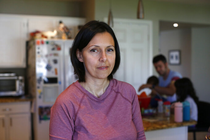 Katherine Rutigliano poses for a portrait in her home in Phoenix, Ariz., on March 15, 2020 photo. When she and her husband moved away from San Francisco in 2013, they figured they would never meet a fellow Democrat again. Rutgliano didn't realize it, but she had moved her family to what is now the front lines in American politics. (AP Photo/Dario Lopez-Mills)