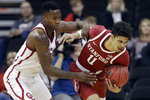 Oklahoma forward Kristian Doolittle, left, tries to steal the ball from Stanford forward Jaiden Delaire (11) during the second half of an NCAA college basketball game Monday, Nov. 25, 2019, in Kansas City, Mo. Stanford won 73-54. (AP Photo/Charlie Riedel)