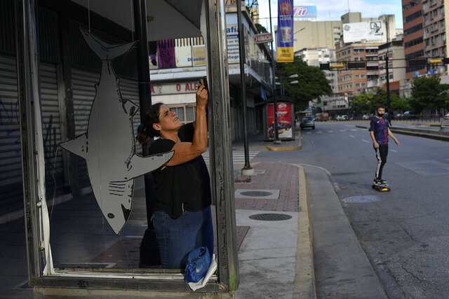 Artist Susan Applewhite attaches her recycled cardboard work art onto a bus stop in the Chacao neighborhood of Caracas, Venezuela, Thursday, Nov. 5, 2020. Her work has evolved from protest art to images of marine life, plants and other images. Applewhite hopes that displaying art in public spaces can help combat crime and motivate people to return to the streets for recreation. (AP Photo/Matias Delacroix)