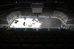 FILE - In this March 12, 2020, file photo, crews cover the ice at American Airlines Center in Dallas, home of the Dallas Stars hockey team, after the NHL season was put on hold due to the coronavirus. The 1919 finals were abandoned after five games due to a flu outbreak. The flu left several Montreal players sickened and eventually killed Joe Hall. It's one of two times since the Stanley Cup was first awarded there was no champion. The memories of that flu outbreak have been brought back to life with the current COVID-19 pandemic and the unknowns of what will happen with this NHL season. (Ashley Landis/The Dallas Morning News via AP, File)