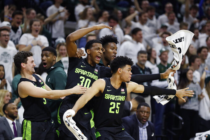 Michigan State guard Foster Loyer (3), and forwards Marcus Bingham Jr. (30), and Malik Hall (25) react after a dunk by teammate Gabe Brown during the second half of an NCAA college basketball game against Charleston Southern, Monday, Nov. 18, 2019, in East Lansing, Mich. (AP Photo/Carlos Osorio)