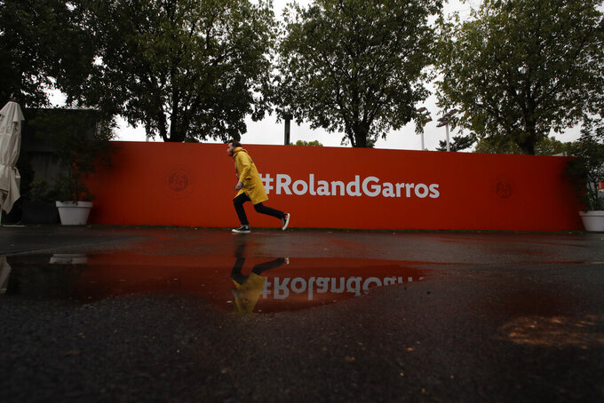 A man in a rain jacket passes a wall during third round matches of the French Open tennis tournament at the Roland Garros stadium in Paris, France, Friday, Oct. 2, 2020. (AP Photo/Alessandra Tarantino)