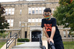 Second grade student Mason Negron, 6, whose mother Kristina Negron was laid off from her job as an aide for a special education class at Schenectady High School, due to budget cuts, poses for a photograph at his Pleasant Valley Elementary school Tuesday, Sept. 29, 2020, in Schenectady, N.Y. (AP Photo/Hans Pennink)