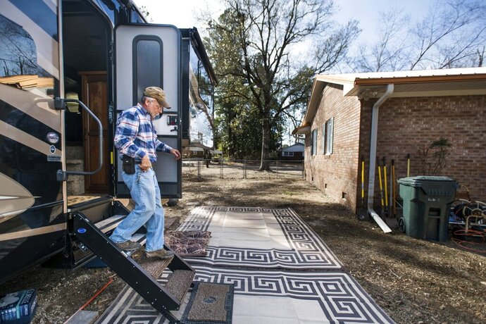 Kevin Tovornik exits his travel camper located in the back yard of his home damaged by flooding from Hurricane Florence near the Crabtree Swamp Friday, Feb. 1, 2019, in Conway, S.C. Tovornik lost his air conditioner and duct work in the 2016 flood. In 2018, he saved his furniture, but still ended up losing the house.