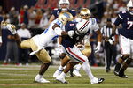 UCLA defensive back Qwuantrezz Knight (24) tackles Arizona wide receiver Stanley Berryhill III (1) during the first half of an NCAA college football game Saturday, Oct. 9, 2021, in Tucson, Ariz. (AP Photo/Chris Coduto)