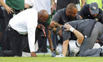 South Florida coach Charlie Strong, left, comforts Central Florida quarterback McKenzie Milton, who had injured his right leg during the first half of an NCAA college football game Friday, Nov. 23, 2018, in Tampa, Fla. (AP Photo/Mike Carlson)
