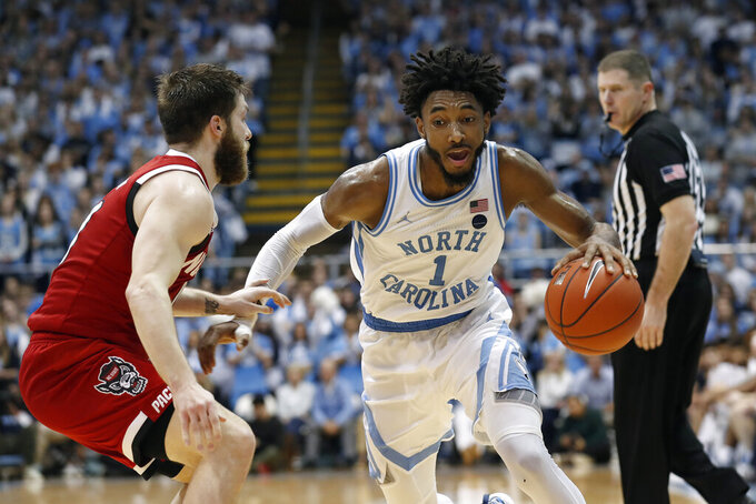 North Carolina guard Leaky Black (1) dribbles while North Carolina State guard Braxton Beverly defends during the first half of an NCAA college basketball game in Chapel Hill, N.C., Tuesday, Feb. 25, 2020. (AP Photo/Gerry Broome)