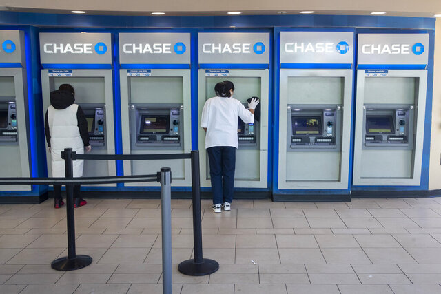 A Chase bank employee, right, disinfects the branches ATMs to fend off coronavirus as a customer uses another along Main St., Tuesday, March 24, 2020, in the Flushing neighborhood of Queens borough of New York. (AP Photo/Mary Altaffer)