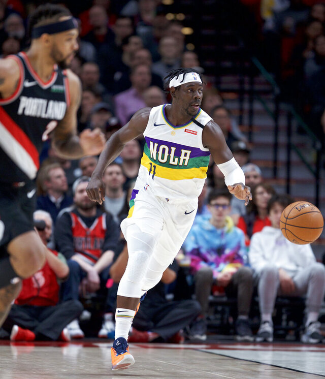 New Orleans Pelicans guard Jrue Holiday, right, bring the ball up during the first half of the team's NBA basketball game against the Portland Trail Blazers in Portland, Ore., Friday, Feb. 21, 2020. (AP Photo/Craig Mitchelldyer)