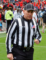In this April 20, 2019, photo, Phillip Davenport walks on the field during Georgia's spring NCAA college football game in Athens, Ga. College football officials travel to the site of a Saturday game on Friday. Crews gather for dinner and meetings Friday night for about 4-5 hours. On Saturday, the crew does another 2-3 hours of prep and film in the morning, before heading to the stadium. Officials get to the stadium about 2 hours before kickoff, survey the field, make sure players behave during warmups and meet briefly with head coaches.  After a 3-plus-hour-game comes what could be the toughest part of the day: The review session with a game day observer on site can take 45 minutes to 2 hours. (Gary McGriff via AP)
