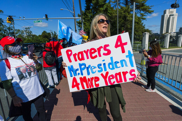 Karen Simon from the District of Columbia, right, together with other supporters of President Donald Trump, gather outside the Walter Reed National Military Medical Center in Bethesda, Md., Monday, Oct. 5, 2020. Trump hoped for a Monday discharge from the military hospital where he is being treated for COVID-19. (AP Photo/Manuel Balce Ceneta)