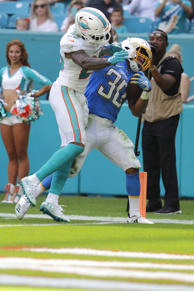 Los Angeles Chargers running back Austin Ekeler (30) scores a touchdown as Miami Dolphins cornerback Xavien Howard (25) attempts to tackle, during the first half at an NFL football game, Sunday, Sept. 29, 2019, in Miami Gardens, Fla. (AP Photo/Lynne Sladky)