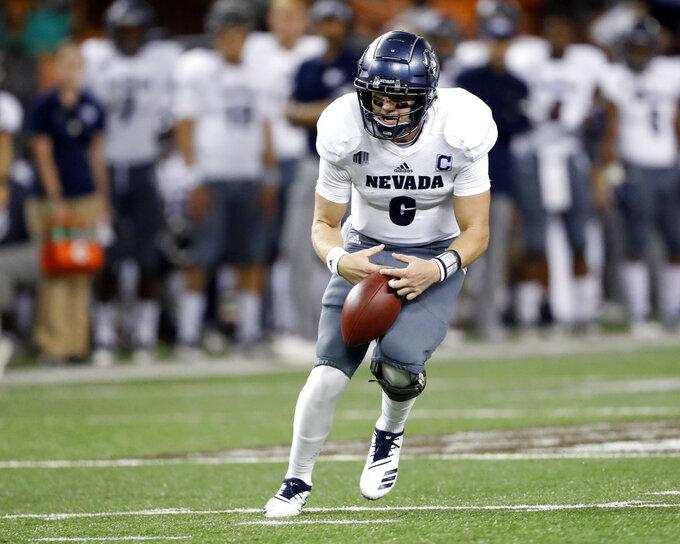 Nevada quarterback Kaymen Cureton (8) fumbles the ball but regains it as he runs against Hawaii during the second quarter of an NCAA college football game, Saturday, Oct. 20, 2018, in Honolulu. (AP Photo/Marco Garcia)