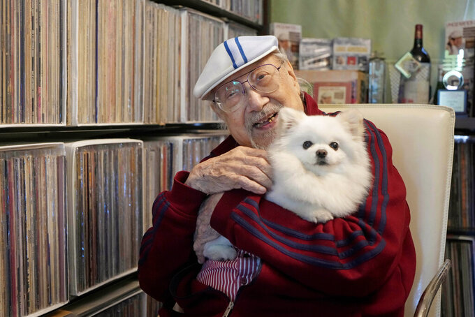 Ray Cordeiro, Hong Kong's oldest DJ, holds his dog at home in Hong Kong, Thursday, May 27, 2021. Cordeiro considers himself the luckiest radio DJ in the world. In a storied career spanning over 70 years in Hong Kong, Cordeiro has interviewed superstars including the Beatles and Elton John, and even received an MBE - an order of the British empire for outstanding achievement or service to the community - from Queen Elizabeth. Cordeiro, who holds the Guinness world record for the world's longest-working DJ, retired last month at the age of 96.(AP Photo/Kin Cheung)