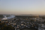 In this Thursday, Feb. 20, 2020, photo, smoke from a pest fumigation rises from the newly constructed Sardar Patel Gujarat Stadium that U.S. President Donald Trump will be visiting, in Ahmedabad, India. A festive mood has enveloped Ahmedabad in India's northwestern state of Gujarat ahead of Prime Minister Narendra Modi's meeting Monday with  Trump, whom he's promised millions of adoring fans. The rally in Modi's home state may help replace his association with deadly anti-Muslim riots in 2002 that landed him with a U.S. travel ban. It may also distract Indians, at least temporarily, from a slumping economy and ongoing protests over a citizenship law that excludes Muslims, but also risks reopening old wounds. (AP Photo/Ajit Solanki)