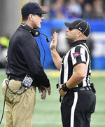 Michigan head coach Jim Harbaugh speaks with an official during the first half of the Peach Bowl NCAA college football game against Florida, Saturday, Dec. 29, 2018, in Atlanta. (AP Photo/Mike Stewart)